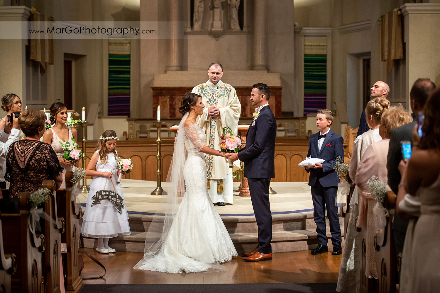 bride and groom holding hands during wedding ceremony at Oakland Church of Saint Leo the Great