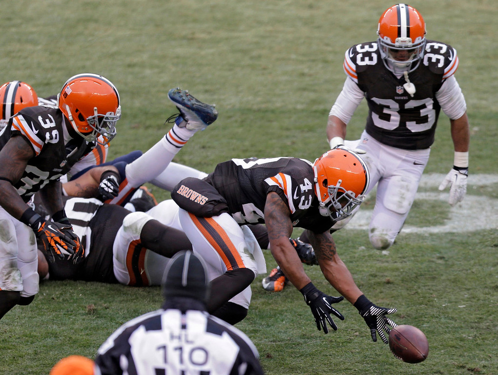 . Cleveland Browns strong safety T.J. Ward (43) recovers a fumble by Chicago Bears tight end Martellus Bennett before returning the ball 51 yards for a touchdown in the third quarter of an NFL football game Sunday, Dec. 15, 2013, in Cleveland. (AP Photo/Tony Dejak)