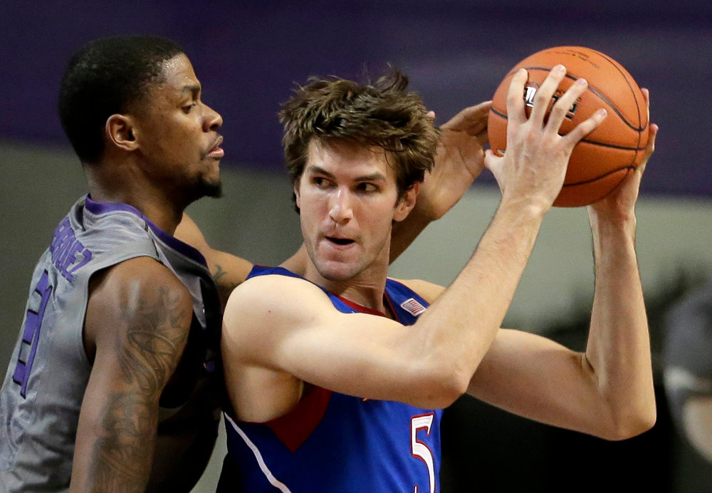 . Kansas State forward Jordan Henriquez, left, tries to steal the ball from Kansas center Jeff Withey during the second half of an NCAA college basketball game Tuesday, Jan. 22, 2013, in Manhattan, Kan. Kansas won 59-55. (AP Photo/Charlie Riedel)
