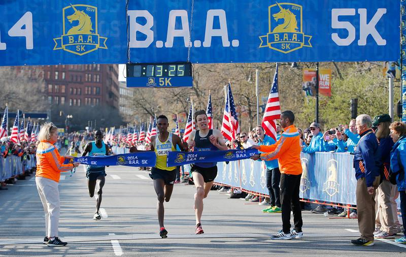 . Dejen Gebremeskel, left, of Ethiopia, breaks the tape ahead of Ben True, of Hanover, N.H., to win the 5-kilometer run Saturday, April 19, 2014, in Boston, in advance of Monday\'s 118th Boston Marathon.  (AP Photo/Elise Amendola)
