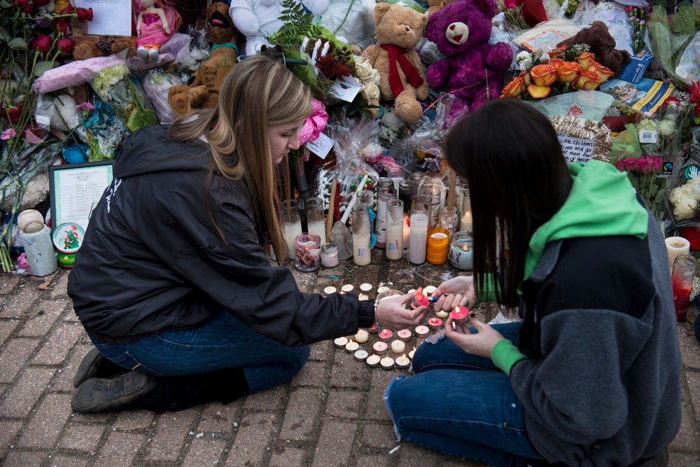 . Two women light candles at a makeshift memorial on December 20, 2012 in Newtown, Connecticut. People continue to mourn the killing of 20 students and 6 adults by gunman Adam Lanza at Sandy Hook Elementary School last December 14.  AFP PHOTO/Brendan  SMIALOWSKI/AFP/Getty Images