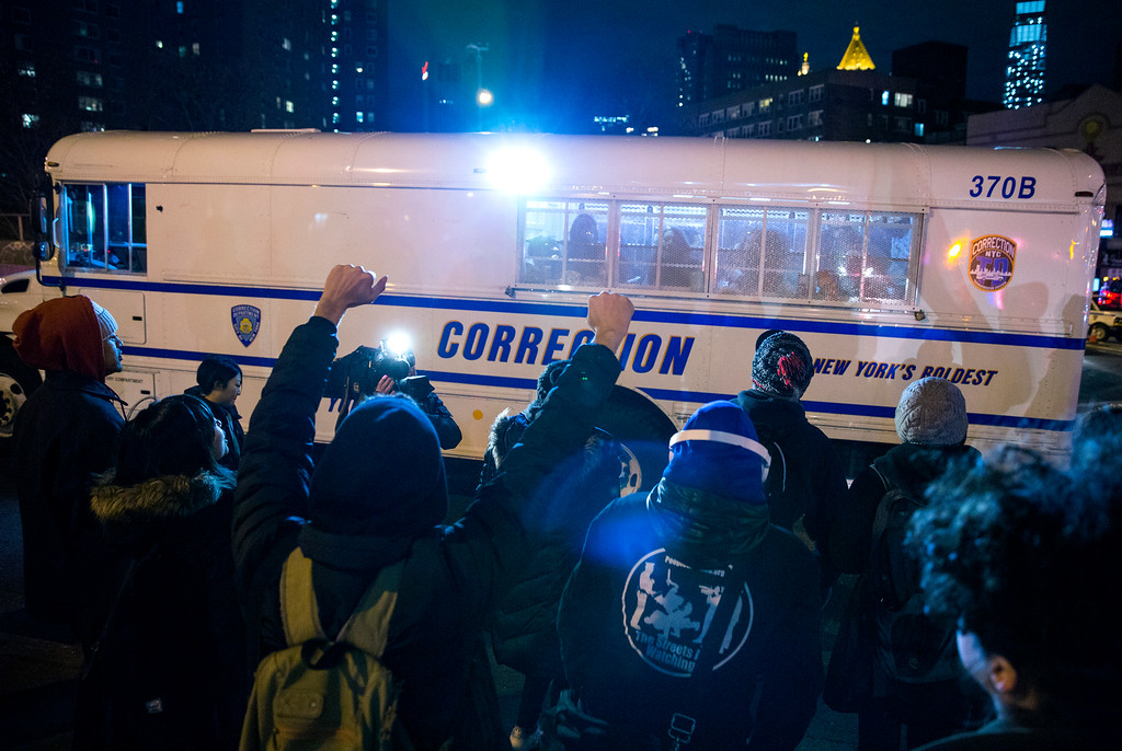 . Fellow protesters cheer those in police custody in a correction bus at the Manhattan side of the Manhattan Bridge Thursday, Dec. 4, 2014, in New York, after several protesters were arrested as they tried to block the bridge entrance protesting against a grand jury\'s decision not to indict the police officer involved in the death of Eric Garner. A grand jury cleared a white New York City police officer Wednesday in the videotaped chokehold death of Garner, an unarmed black man, who had been stopped on suspicion of selling loose, untaxed cigarettes, a lawyer for the victim\'s family said. (AP Photo/Craig Ruttle)