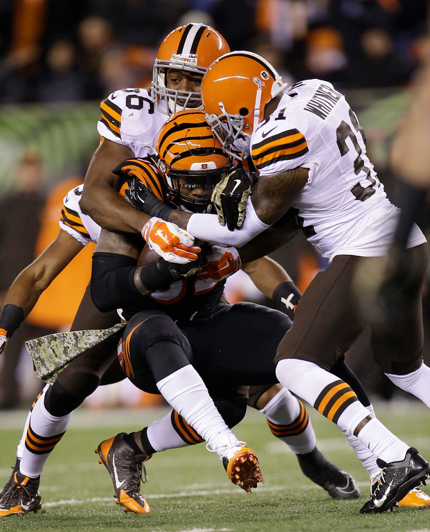 . Cincinnati Bengals running back Jeremy Hill (32) is tackled by Cleveland Browns\' Karlos Dansby (56) and Donte Whitner (31) during the first half of an NFL football game Thursday, Nov. 6, 2014, in Cincinnati. (AP Photo/AJ Mast)