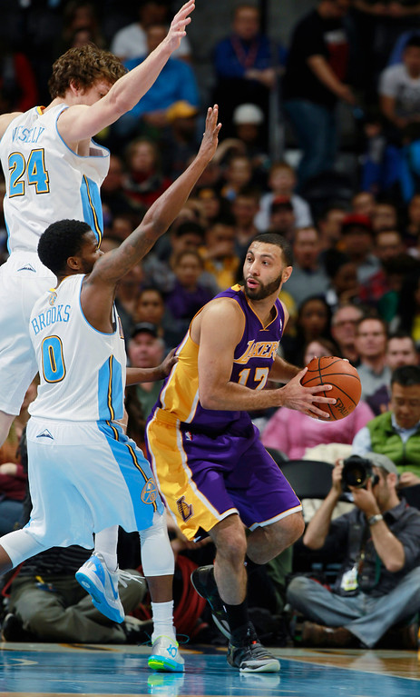 . Los Angeles Lakers guard Kendall Marshall, right, is trapped with ball by Denver Nuggets guard Aaron Brooks, front left, and forward Jan Vesely, of the Czech Republic, in the fourth quarter of the Nuggets\' 134-126 victory in an NBA basketball game in Denver on Friday, March 7, 2014. (AP Photo/David Zalubowski)