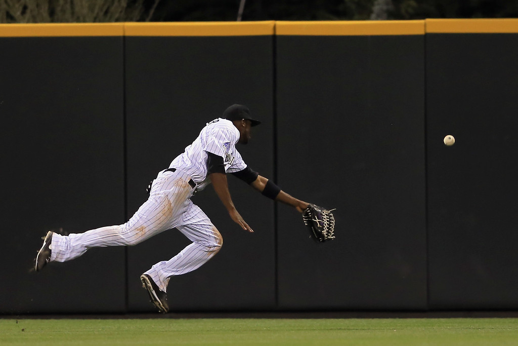 . DENVER, CO - AUGUST 10:  Centerfielder Dexter Fowler #24 of the Colorado Rockies can\'t catch a triple by Garrett Jones #46 of the Pittsburgh Pirates that scored Russell Martin of the Pirates to take a 2-1 lead over the Colorado Rockies in the sixth inning at Coors Field on August 10, 2013 in Denver, Colorado.  (Photo by Doug Pensinger/Getty Images)