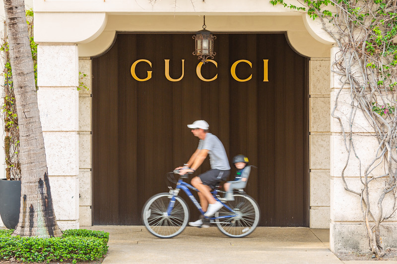 A bicyclist and his child ride up the sidewalk in front of the Gucci store on Worth Avenue in Palm Beach, Friday, April 24, 2020. The stores on Worth Avenue have been closed due to the coronavirus pandemic. [JOSEPH FORZANO/palmbeachdailynews.com]