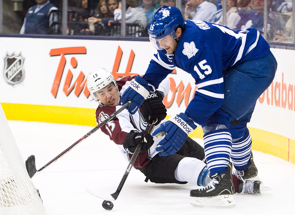 . Toronto Maple Leafs defenseman Paul Ranger, right, competes for the loose puck with Colorado Avalanche forward PA Parenteau, left, during the third period of an NHL hockey game in Toronto on Tuesday, Oct. 8, 2013. Colorado won 2-1. (AP Photo/The Canadian Press, Nathan Denette)