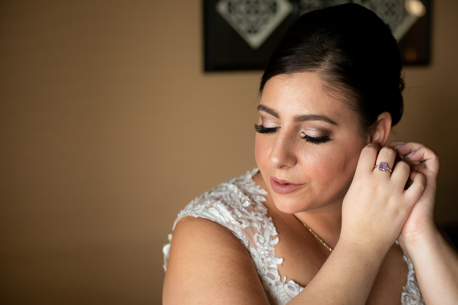 bride in a white lace dress putting her earrings on just before her wedding