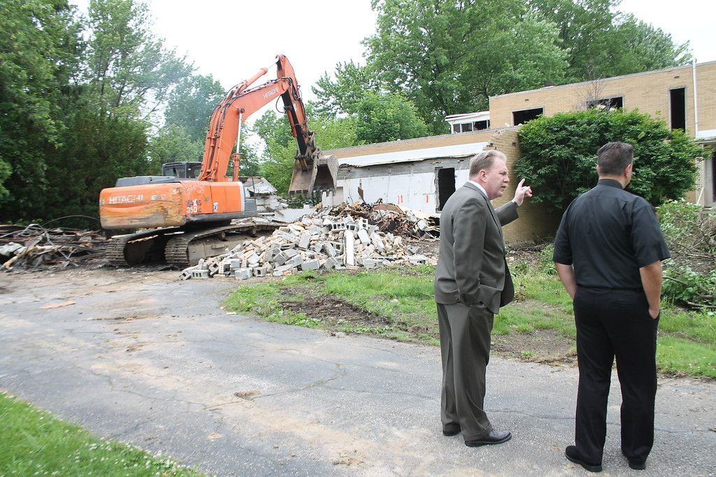 . State Representative John Rogers and Parish Priest, Father Steve Breck look on as demolition begins on the rectory of Saint Mary Magdalene\'s in Willowick on June 11. Kristi Garabrandt - The News-Herald
