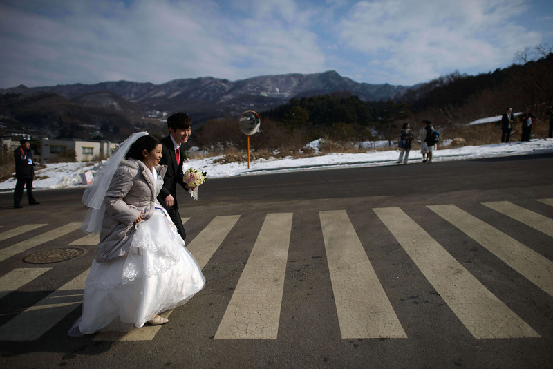 ". A newly-wed cross a road following a mass wedding event held by the Unification Church in Gapyeong on February 12, 2014. Unification Church members forming 2500 couples from 52 countries were married in a mass wedding in South Korea -- only the second such event since the death of their ""messiah\"" and controversial church founder Sun Myung Moon. (ED JONES/AFP/Getty Images)"