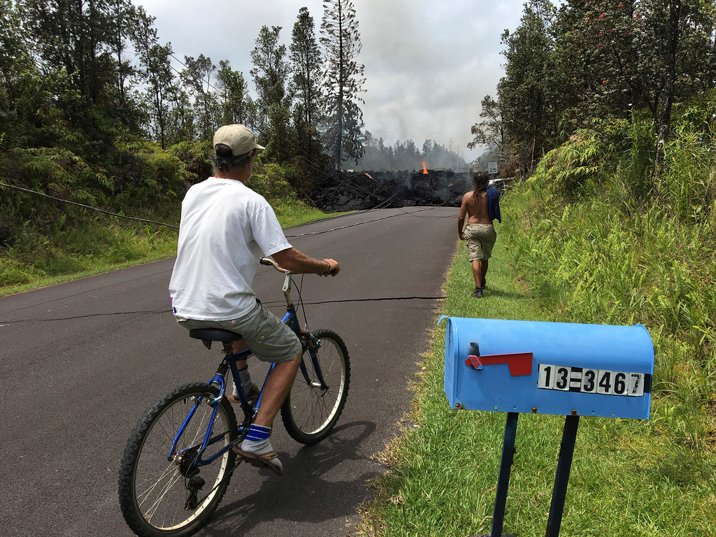 . Resident Sam Knox rides his bicycle to the edge of the road as lava burns across the road in the Leilani Estates in Pahoa, Hawaii, Saturday, May 5, 2018. Hundreds of anxious residents on the Big Island of Hawaii hunkered down Saturday for what could be weeks or months of upheaval as the dangers from an erupting Kilauea volcano continued to grow. (AP Photo/Marco Garcia)