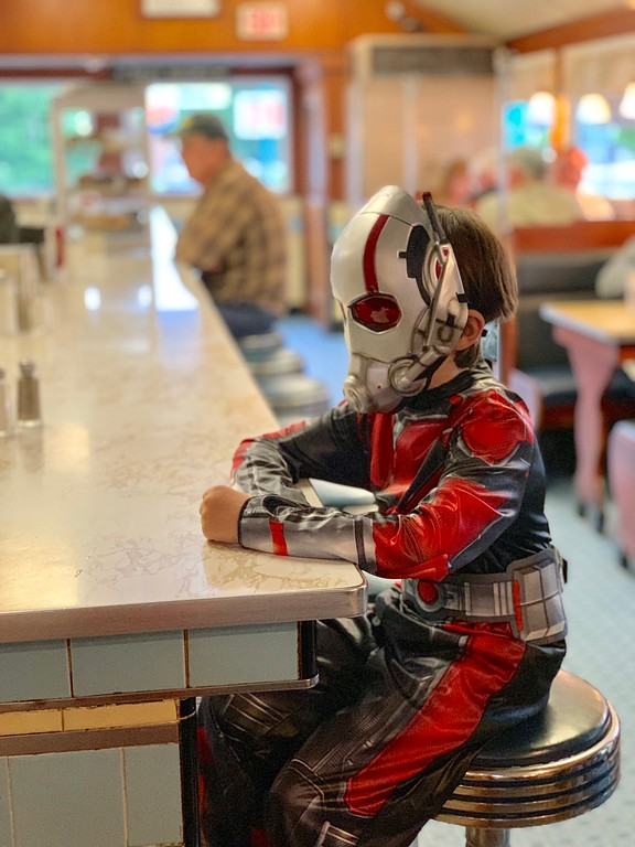 boy dressed as Ant-Man in diner