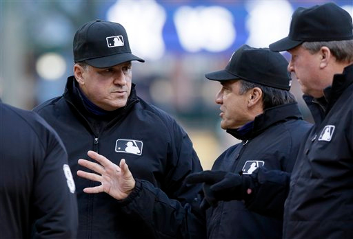 . Umpire Tony Randazzo, left, talks with umpire Phil Cuzzi, center, and Gerry Davis, right, before the baseball game between the Detroit Tigers and the New York Yankees, Tuesday, April 21, 2015, in Detroit. (AP Photo/Carlos Osorio)