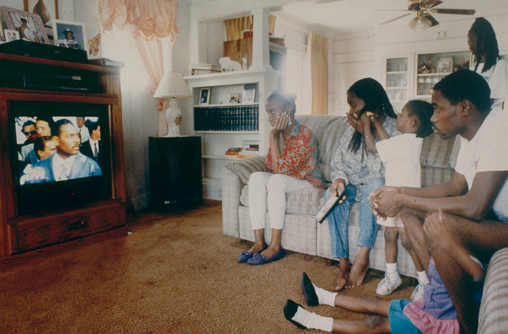 ". A family in South Central Los Angeles gathered in front of their television to listen to Rodney King give a press conference. King uttered the phrase that would become a mantra for healing when he asked, ""... can we all get along.\"" May 1, 1992. (Photo by John McCoy/Los Angeles Daily News)"