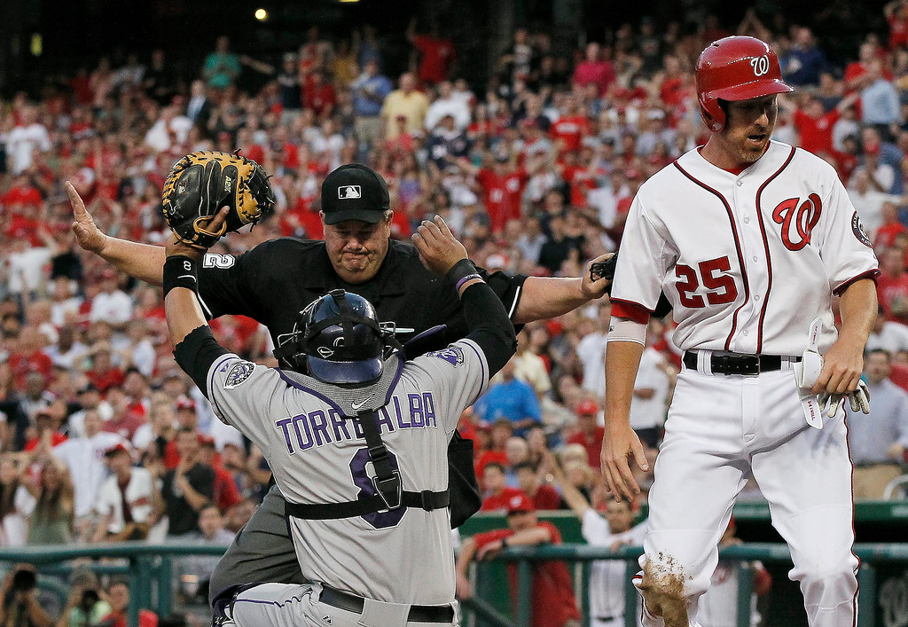 . Home plate umpire Joe West calls Washington Nationals first baseman Adam LaRoche (25) safe at the plate as Colorado Rockies catcher Yorvit Torrealba (8) holds the ball up during the fourth inning of a baseball game at Nationals Park, Thursday, June 20, 2013, in Washington. (AP Photo/Alex Brandon)