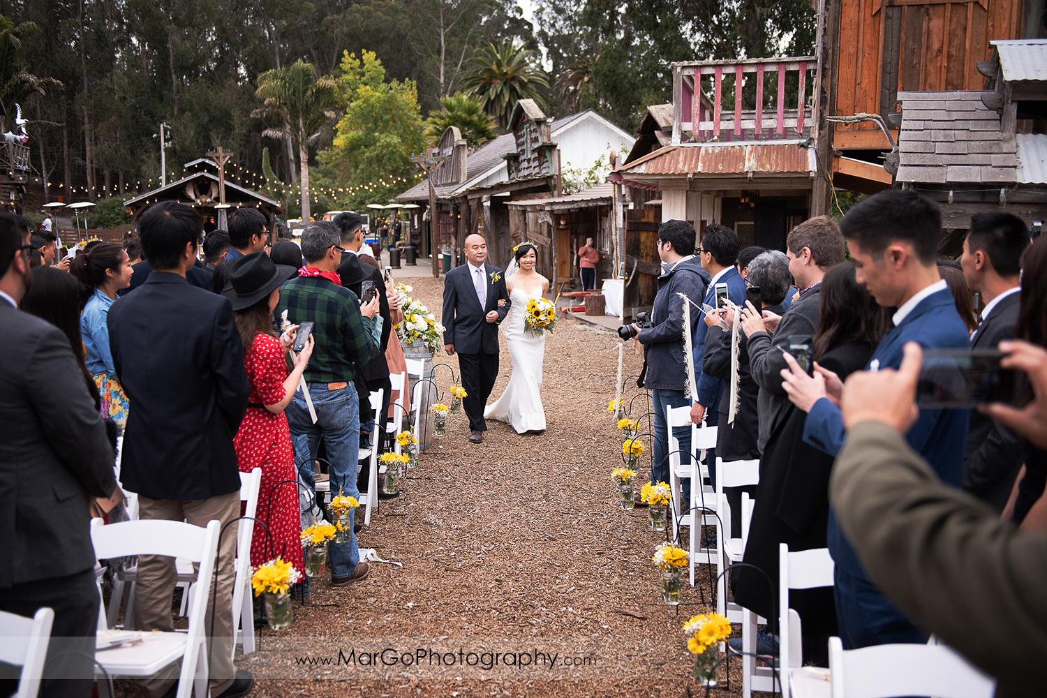 bride walking down the aisle with her father during wedding ceremony at Long Branch Saloon & Farms in Half Moon Bay