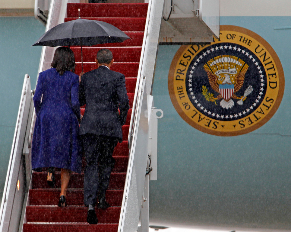 . President Barack Obama and first lady Michelle Obama walk up the stairs of Air Force One at Andrews Air Force Base, Md. Thursday, April 18,  2013.  ( AP Photo/Jose Luis Magana)