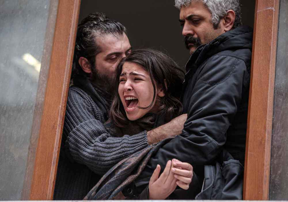 . Family members cry as people carry the coffin of Berkin Elvan, a Turkish teenager who was in a coma since being hit in the head by a tear gas canister fired by police during the summer\'s anti-government protests, in Istanbul, Turkey, Tuesday, March 11, 2014. The 15-year old Berkin Elvan�s death in an Istanbul hospital nine months after he fell into a coma looked likely to spark new protests in Turkey. Elvan, who turned 15 in January was caught up in the protests on his way to a shop to buy bread.(AP Photo/Emrah Gurel)