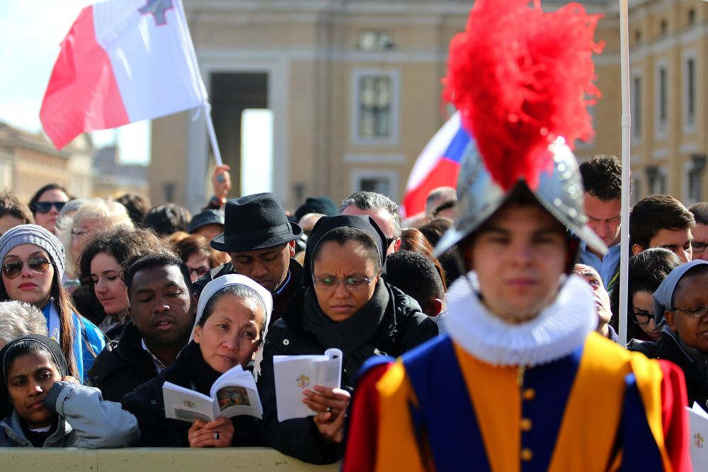 . Wellwishers look on during the Inauguration Mass for Pope Francis in St Peter\'s Square on March 19, 2013 in Vatican City, Vatican. The mass is being held in front of an expected crowd of up to one million pilgrims and faithful who have filled the square and the surrounding streets to see the former Cardinal of Buenos Aires officially take up his role as pontiff. Pope Francis� inauguration takes place in front of Cardinals and spiritual leaders as well as heads of state from around the world.  (Photo by Joe Raedle/Getty Images)