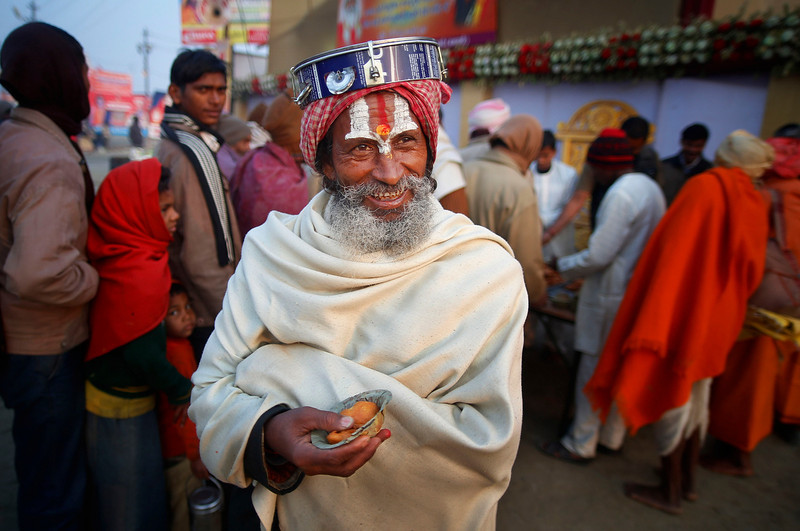 . A Hindu holy man smiles as he walks back after receiving charitable food  during the Maha Kumbh festival in Allahabad, India, Tuesday, Jan. 29, 2013. Millions of Hindu pilgrims are expected to attend the Maha Kumbh festival, which is one of the world\'s largest religious gatherings that lasts 55 days and falls every 12 years. During the festival pilgrims bathe in the holy Ganges River in a ritual they believe can wash away their sins. (AP Photo/Saurabh Das)
