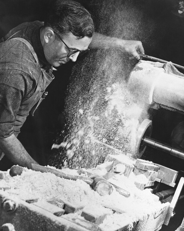 . Powdered Micarta plastic flies like snow from a milling machine as slots are grooved in an insulator support for overhead trolley wires at the Westinghouse plant in this suburb of Pittsburgh, Pennsylvania Jan. 21, 1942. Made of layers of resin-treated cloth or paper moulded under 225-ton pressure, Micarta is used for bearings, gears and in planes, ships and guns. (AP Photo)