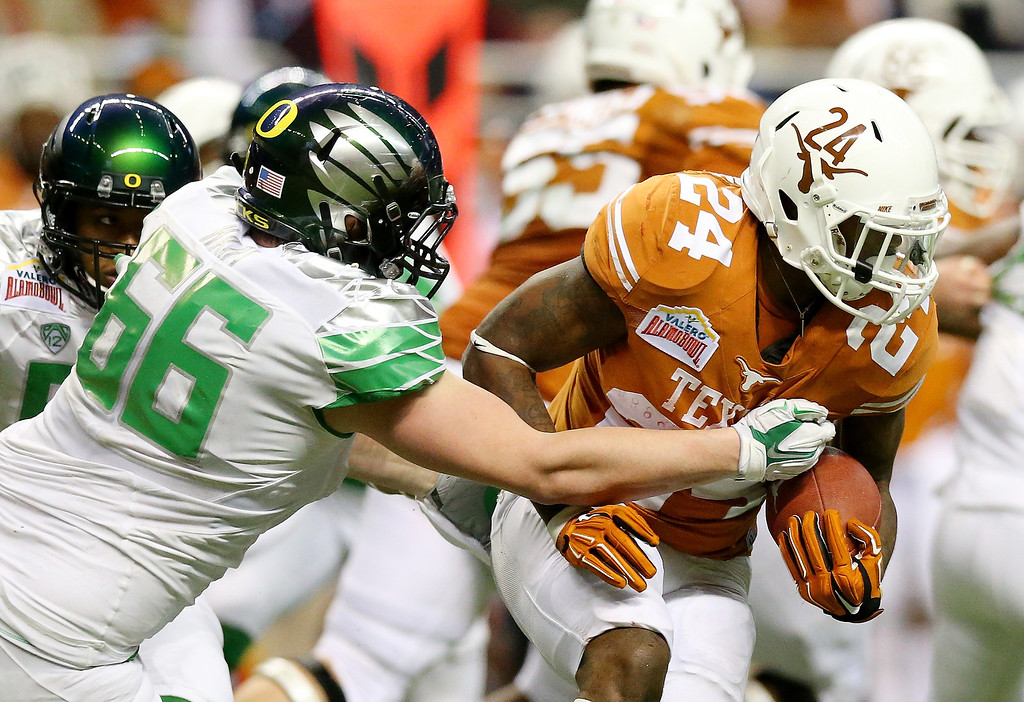 . Running back Joe Bergeron #24 of the Texas Longhorns carries the ball as defensive tackle Taylor Hart #66 of the Oregon Ducks defends during the Valero Alamo Bowl at the Alamodome on December 30, 2013 in San Antonio, Texas.  (Photo by Ronald Martinez/Getty Images)
