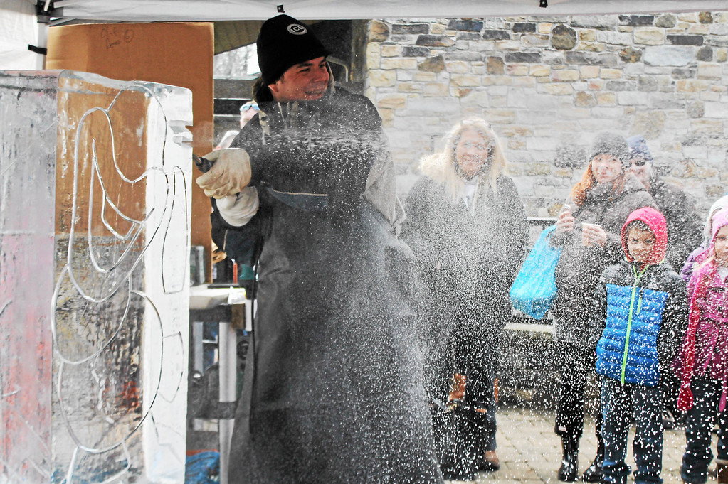 . George Niemoeller of Elegant Ice Creations sprays ice shavings while carving an ice sculpture of Olaf during the 2017 Frozen Fest. This year\'s event is Jan. 28. For more information, visit www.geaugaparkdistrict.org. (Kristi Garabrandt/The News-Herald)