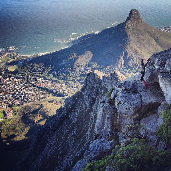 Abseiling down Table Mountain w/a view of Lion's Head. I kid, but the climber with the gear is not.