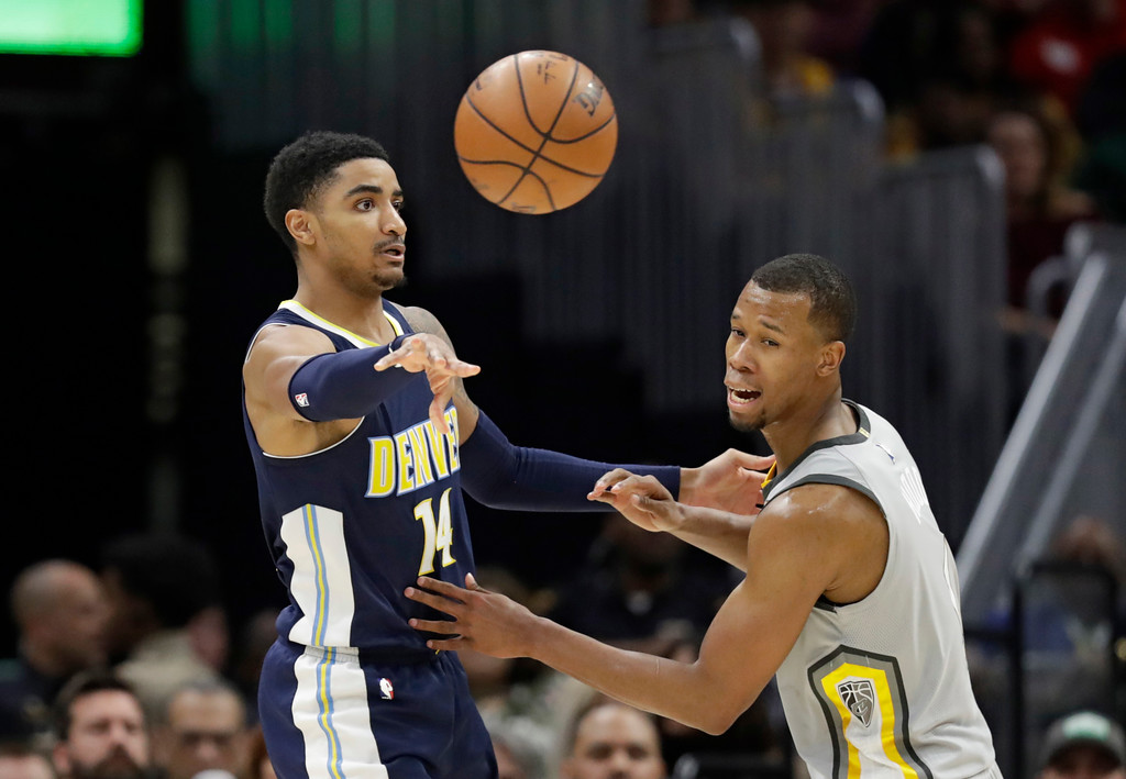 . Denver Nuggets\' Gary Harris, left, passes against Cleveland Cavaliers\' Rodney Hood (1) in the first half of an NBA basketball game, Saturday, March 3, 2018, in Cleveland. (AP Photo/Tony Dejak)