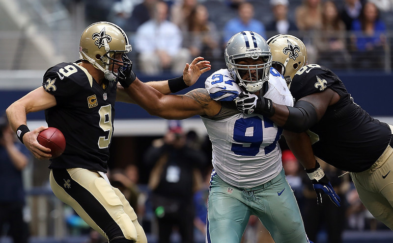 . Defensive end Jason Hatcher #97 of the Dallas Cowboys beats out guard Ben Grubbs #66 of the New Orleans Saints to force quarterback Drew Brees #9 of the New Orleans Saints to scramble with the ball at Cowboys Stadium on December 23, 2012 in Arlington, Texas.  (Photo by Tom Pennington/Getty Images)