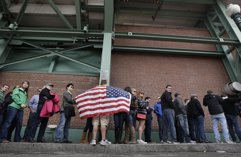 . Adam Comeau, 17, hold a U.S. flag as he waits in line to enter Fenway Park before the start of a baseball game between the Kansas City Royals and the Boston Red Sox, the first game held in the city following the Boston Marathon explosions, Saturday, April 20, 2013, in Boston.  Police captured Dzhokhar Tsarnaev, 19, the surviving Boston Marathon bombing suspect, late Friday, after a wild car chase and gun battle earlier in the day left his older brother dead. (AP Photo/Julio Cortez)