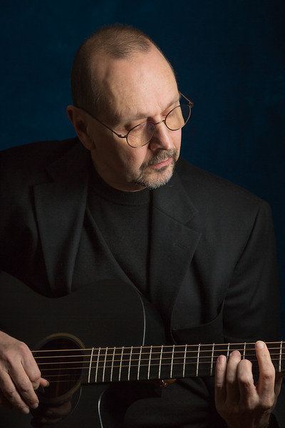 Musician Jeff Zuber playing his guitar in the photo studio and singing a song.