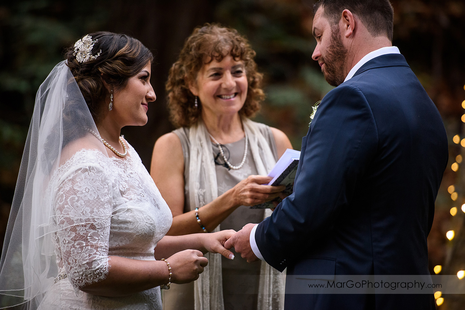 bride putting ring on groom's finger during wedding ceremony at Saratoga Springs Cathedral Grove
