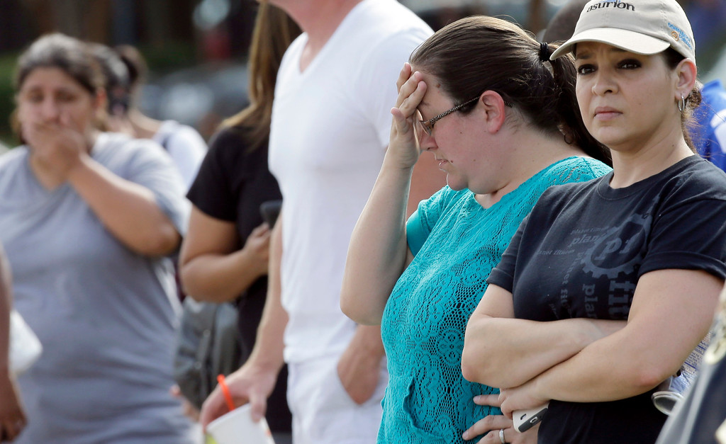 . Carrie Estrada, right, and Mindy Weaver, second from right, wait for their children outside Spring High School Wednesday, Sept. 4, 2013, in Spring, Texas.  (AP Photo/David J. Phillip)