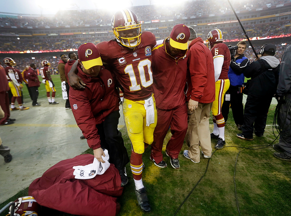 Description of . Washington Redskins quarterback Robert Griffin III is helped off the field after an injury during the second half of an NFL football game against the Baltimore Ravens in Landover, Md., Sunday, Dec. 9, 2012. Griffin suffered a sprained knee at the end of a 13-yard scramble. The Redskins won 31-28. (AP Photo/Patrick Semansky)