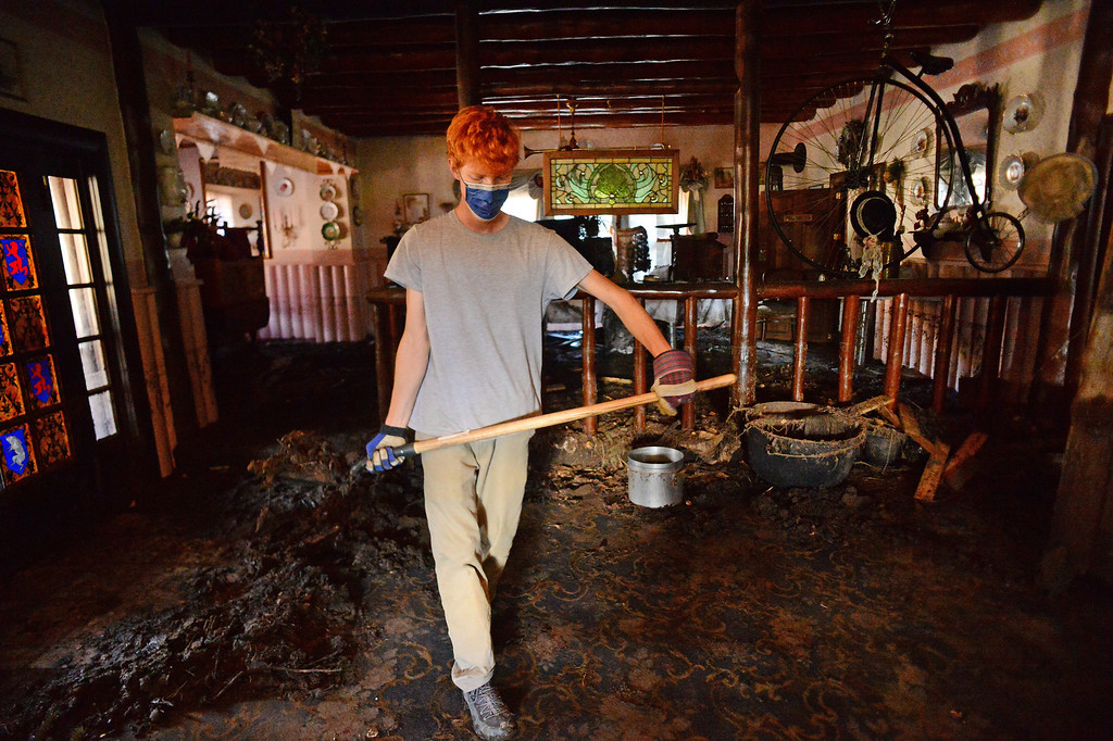 . GLEN HAVEN, CO - OCTOBER 8: Volunteer Caleb Johnson picks up a shovelful of mud  up off the carpet to throw out of the window at the historic Glen Haven Inn in Glen Haven, CO on October 8, 2013.  The Inn was one of the only businesses that actually made it in the town but has been inundated with mud and debris.  The water line along the walls suggest that the flood waters reached at least four feet inside the building.  (Photo By Helen H. Richardson/ The Denver Post)