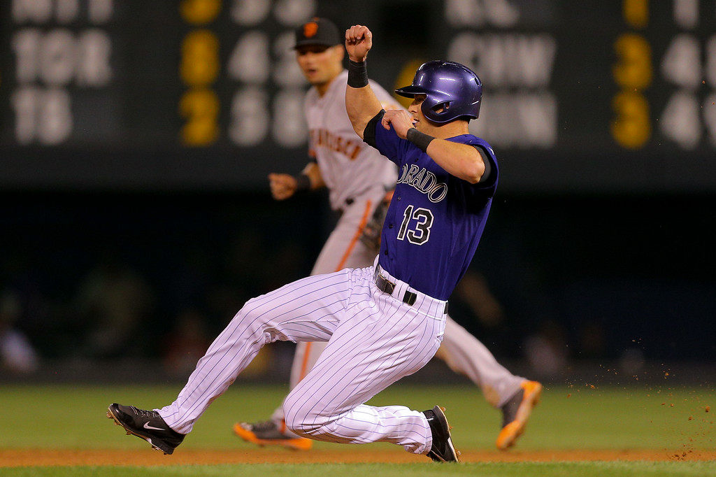 . DENVER, CO - SEPTEMBER 2:  Drew Stubbs #13 of the Colorado Rockies steals second base against the San Francisco Giants looks on during the fifth inning at Coors Field on September 2, 2014 in Denver, Colorado. (Photo by Justin Edmonds/Getty Images)