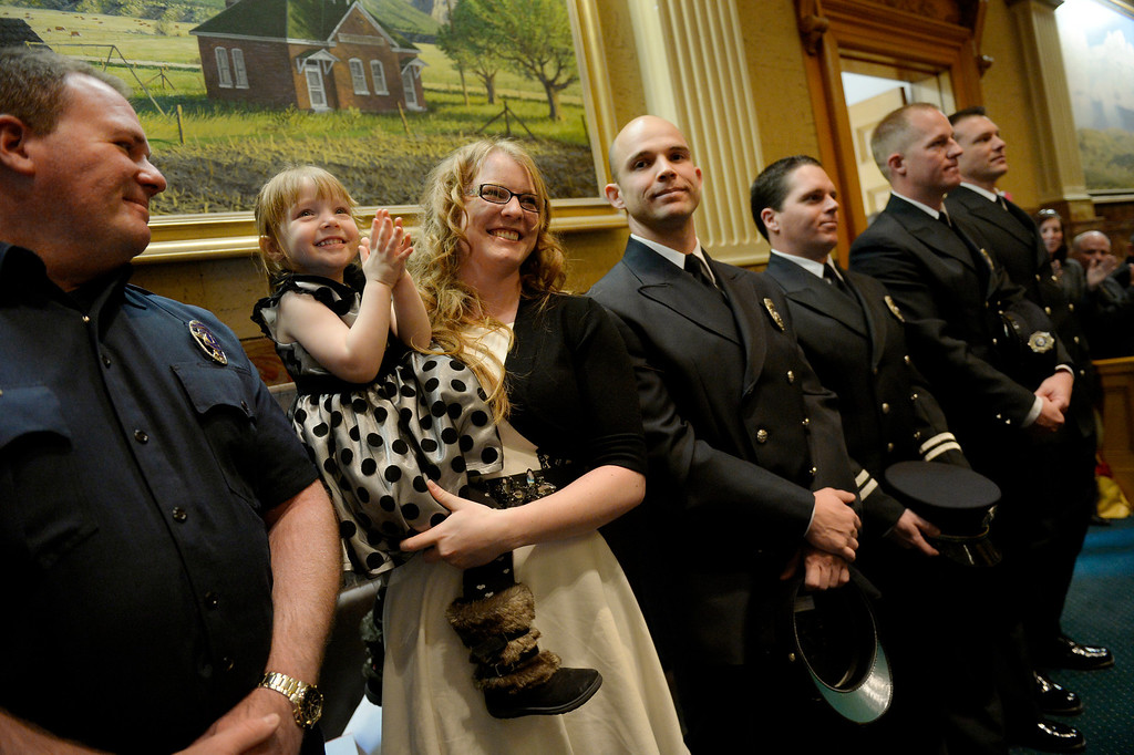 ". DENVER, CO. - JANUARY 08: Erin Brazzil stands with her daughter, Autumn, 3, and first responders (l-r) Mike Becker, of the Longmont Fire Department and Sean Tallman, Chad Rademacher, James Wood and Steve Knoll of the Mountain View Fire Department in the House of Representatives during the first day of the new legislative session at the Colorado Capitol in Denver, CO January 08, 2014. House Speaker Mark Ferrandino recognized the firefighters for saving Brazzil from her water engulfed car in Longmont during flooding on September 12, 2013. In his speech Ferrandino told their story, ""On September 12th Erin Brazzil was driving across Longmont to pick up her young daughter when a wall of water engulfed her Nissan Altima. It lost power and began to fill with water. She called 9-1-1.  When several rescuers,including Lieutenant Mike Becker and his crew from the Longmont Fire Department, were finally able to locate the car, it was barely visible,nearly submerged.Erin�s breathing space had been reduced to a few inches at the roof of the car.  Three members of the Mountain View Fire Rescue-- Captain Chad Rademacher, Steve Knoll and Sean Tallman � struggled through the rising waters to reach the car.  The responders had to pry off the windshield and lift Ms. Brazzil out of the car, and Mountain View fire medic Jamie Wood, riding a personal watercraft � that�s right, a Jetski � took her to safety.   Erin and her rescuers are with us today. Please join me in thanking all the first responders who showed such ingenuity and bravery during the storms.  Without them, it�s unimaginable how much worse it could have been.\"" (Photo By Craig F. Walker / The Denver Post)"