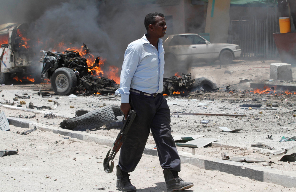 . A policeman walks past the scene of an explosion near the presidential palace in Mogadishu March 18, 2013. A car bomb exploded near the presidential palace in the Somali capital Mogadishu on Monday, killing at least 10 people in a blast that appeared to target senior government officials, police said. REUTERS/Feisal Omar