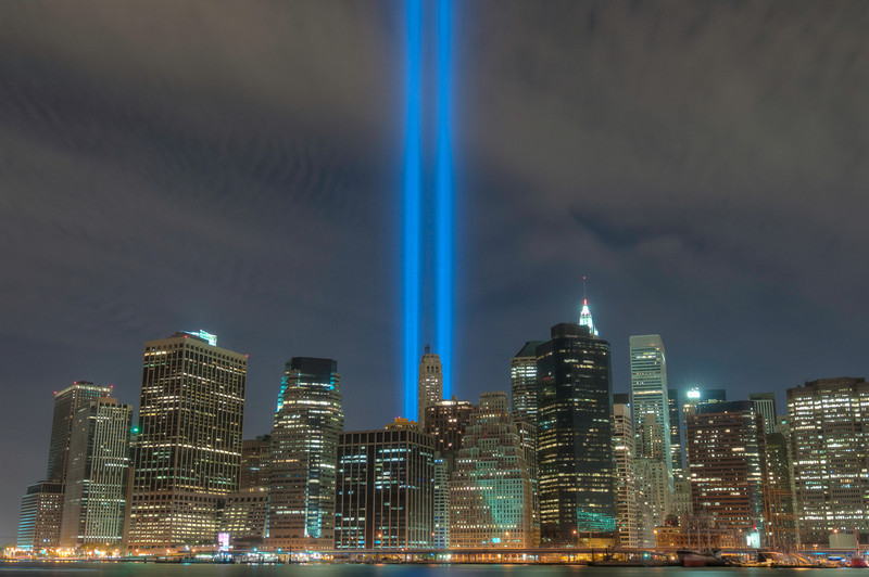 These are the September 11th Tribute Lights from Brooklyn Bridge Park on September 11th, 2010.  Please share this with your friends.    The Tribute in Light is an art installation of 88 searchlights placed next to the site of the World Trade Center to create two vertical columns of light in remembrance of the September 11 attacks. It initially ran as a temporary installation from March 11 to April 14, 2002, and was launched again in 2003 to mark the second anniversary of the attack. As of 2012, it has been repeated every year on September 11.  There are also some panoramic photos here: http://www.robertcain.info/Photography/Panoramas/1189645_Tpq3ns#!i=371040955&k=djtH9