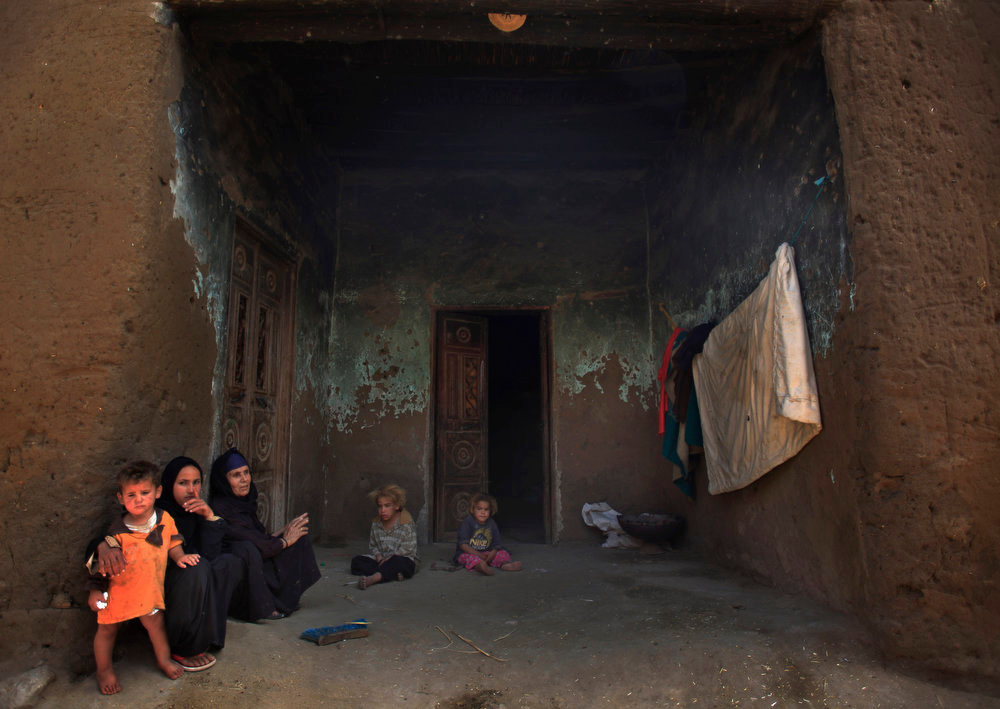 . A Palestinian refugee family sits outside of their house in Gezirat al-Fadel village, Sharqiya, about 150 kilometers (93 miles) east of Cairo, Egypt.  (AP Photo/Khalil Hamra)