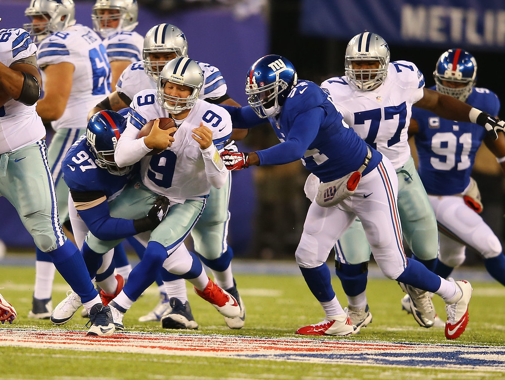 . Tony Romo #9 of the Dallas Cowboys is sacked by  Linval Joseph #97 and  Spencer Paysinger #54 of the New York Giants during their game at MetLife Stadium on November 24, 2013 in East Rutherford, New Jersey.  (Photo by Al Bello/Getty Images)