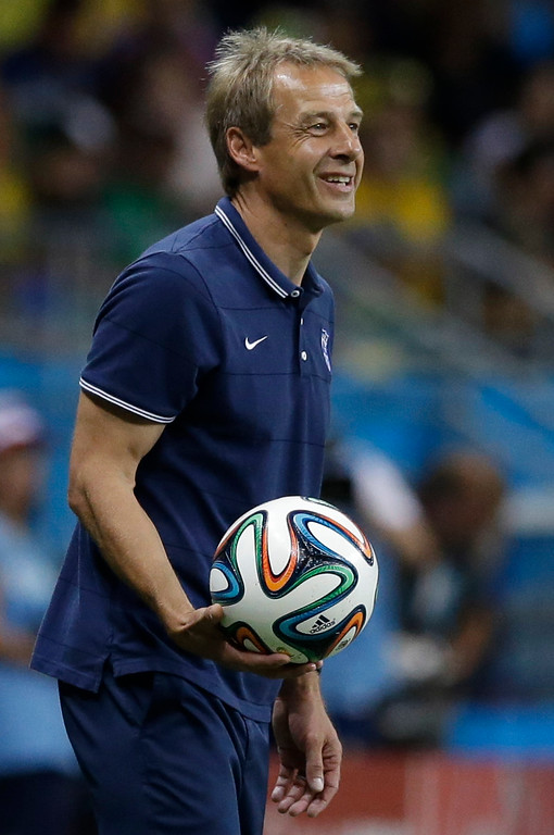 . United States\' head coach Juergen Klinsmann smiles as he holds the ball during the World Cup round of 16 soccer match between Belgium and the USA at the Arena Fonte Nova in Salvador, Brazil, Tuesday, July 1, 2014. (AP Photo/Matt Dunham)