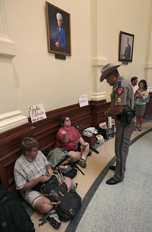 ". A Department of Public Safety officer asks Lainie Duro of Occupy Austin to move her ""People\'s Library\"" set up under the portrait of former Gov. Ann Richards at the Texas State capitol on July 1, 2013 in Austin, Texas. This is the first day of a second legislative special session called by Texas Gov. Rick Perry to pass a restrictive abortion law through the Texas legislature. The first attempt was defeated after opponents of the law were able to stall the vote until after first special session had ended.  (Photo by Erich Schlegel/Getty Images)"