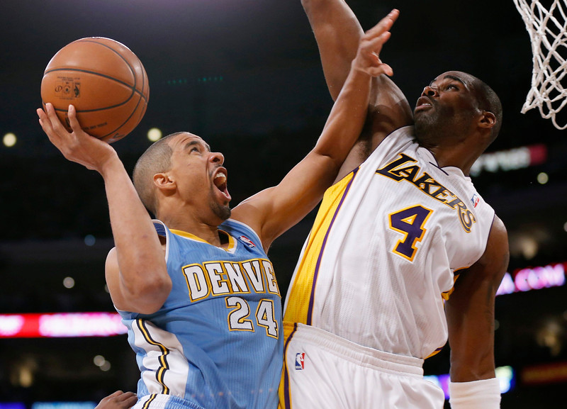 . Denver Nuggets\' Andre Miller (L) goes to the basket as Los Angeles Lakers\' Antawn Jamison (R) defends during the first half of their NBA basketball game in Los Angeles January 6, 2013. REUTERS/Danny Moloshok