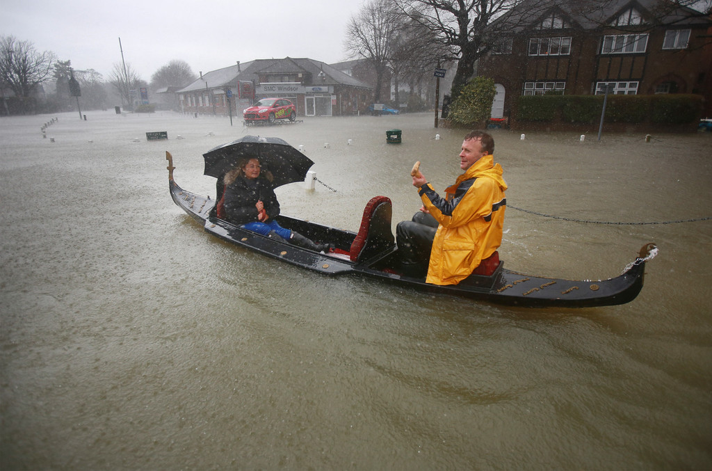 . A couple promote the Piccola Venezia Italian restaurant by rowing their gondola through flood waters on February 12, 2014 in Datchet, England.The Environment Agency contiues to issue severe flood warnings for a number of areas on the river Thames in the commuter belt west of London. With heavier rains forecast for the coming week people are preparing for the water levels to rise.  (Photo by Peter Macdiarmid/Getty Images)
