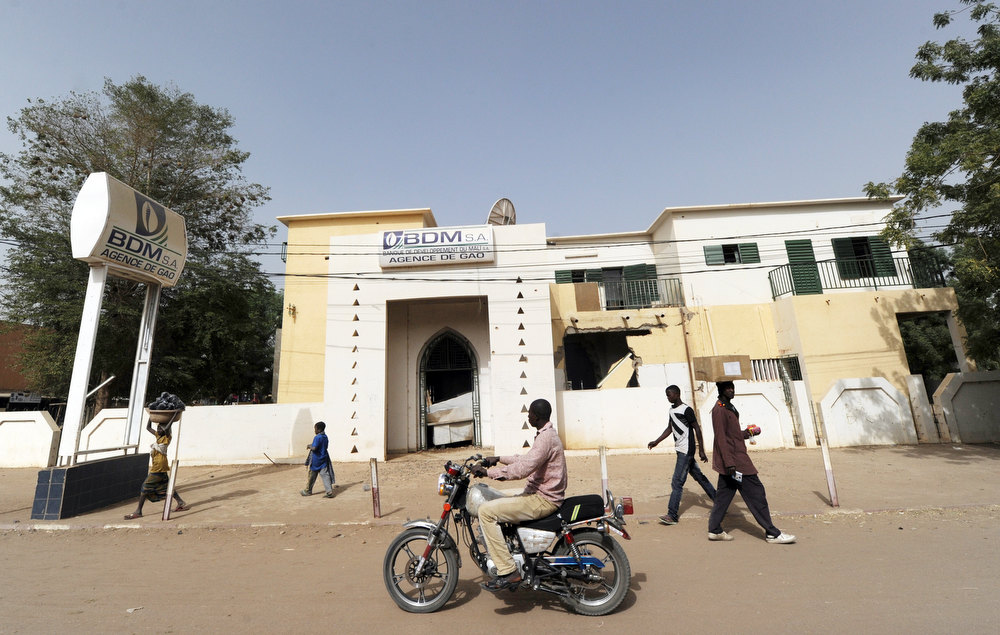. People walk past a bank looted by the rebels of the Movement for Oneness and Jihad in West Africa (MUJAO) in Gao, on February 1, 2013. President Francois Hollande visits Mali on February 2, as French-led troops worked to secure the last Islamist stronghold in the north after a lightning offensive against the extremists. Gao\'s light-skinned Arab and Tuareg residents face the violent anger of their black neighbours since French and Malian troops reclaimed the city from the rebels of the Movement for Oneness and Jihad in West Africa (MUJAO) on January 26. SIA KAMBOU/AFP/Getty Images