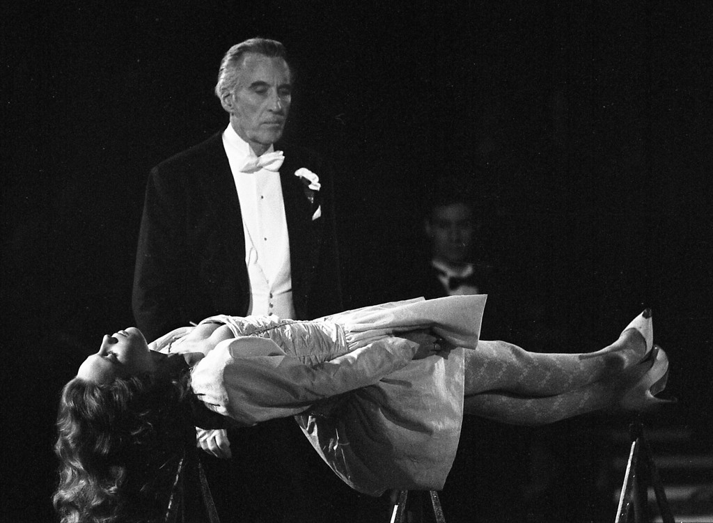 ". In this file photo dated December 5, 1987, the lights were turned down low as British actor Christopher Lee performs as magician in the act ""The Floating Virgin\"" with German actress Marie-Theres Relin, daughter of Maria Schell, during the charity function \""Stars in der Manege\"" (Stars in the Arena) in the tent of Circus Krone in Munich, West Germany. (AP Photo/Uwe Lein, FILE)"