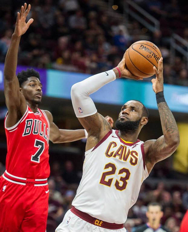 . Cleveland Cavaliers\' LeBron James (23) shoots past Chicago Bulls\' Justin Holiday (7) during the first half of an NBA preseason basketball game in Cleveland, Tuesday, Oct. 10, 2017. (AP Photo/Phil Long)