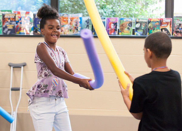 06/28/18 Wesley Bunnell | Staff Kamilha Collazio, age 11, plays pool noodle joust with Justin Bridge, age 9, at the Tween Time Olympics at the New Britain Public Library on Thursday afternoon. The event is designed to bridge the gap from youth to teen events in the library.